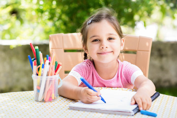 Little Girl Drawing Picture Outdoors In Garden