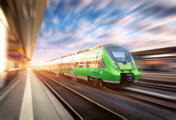 High speed train in motion at the railway station at sunset in Europe. Beautiful green modern train on the railway platform with motion blur effect. Industrial scene with passenger train on railroad