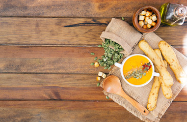 Sweet potato carrot soup on a wood background.