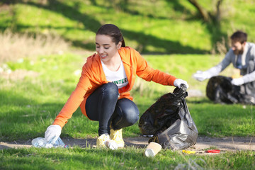 Young beautiful volunteer picking up litter in park