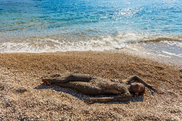 Beautiful woman laying on the beach and sea waves splash near her.Top view. Woman smearing mud mask on body, Spa outdoor and cosmetics. Recreation tourism and lifestyle, body care, natural therapy.