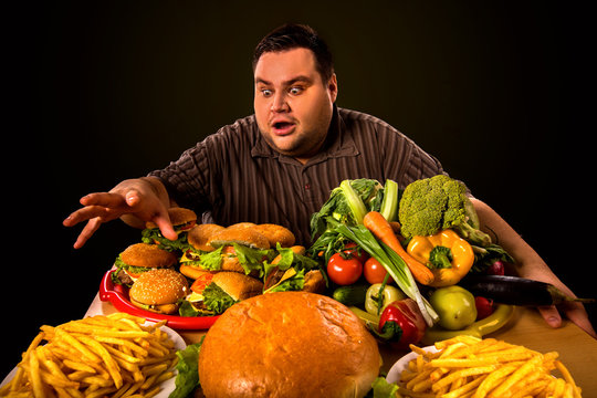 Diet fat man who makes choice between healthy and unhealthy food . Overweight male with hamburgers, french fries and vegetables trays trying to lose weight first time .Abundance of food concept.