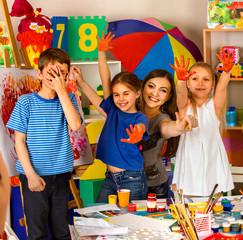 Children painting finger on easel. Small students hands up in art school class. Cheers children in kindergarten. Craft drawing education develops creative abilities of children.