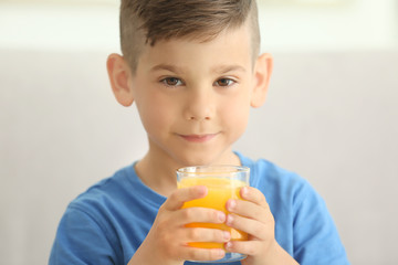 Cute little boy with glass of juice at home, closeup