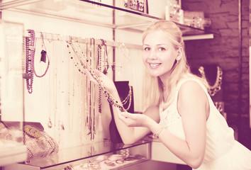 girl customer choosing necklace.
