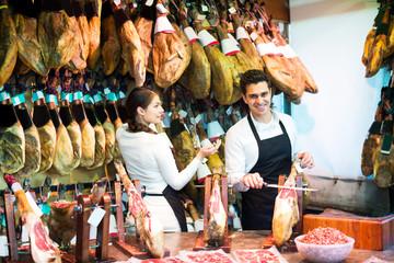 Portrait of sellers offering tasty jamon