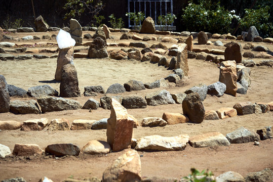 Large stone and sand labyrinth bathed in mid-day sunlight; crystal center stone to gather your thoughts
