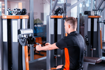 Handsome young fit man training on modern row machine in gym