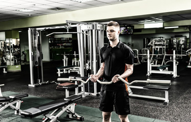 Handsome sportive man in sportswear lifting barbell