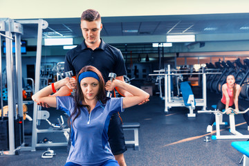 Male couch trains young woman in sportswear lifting some weights
