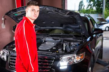 Male motor mechanic in uniform standing near a black sedan