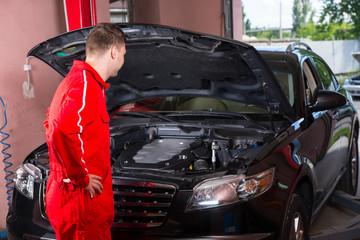 Young male motor mechanic in uniform standing near a black sedan