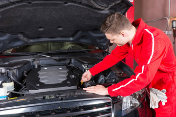 Male motor mechanic is going to check the oil level in a car