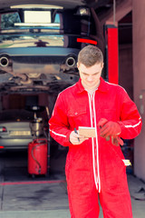 Young male auto mechanic standing making notes