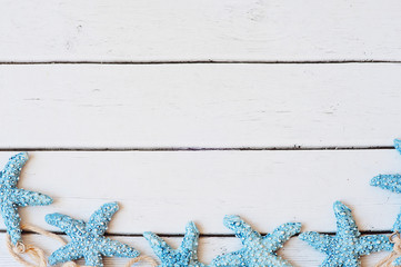 Marine items sea stars on wooden background. Sea objects on turquoise painted wooden planks. Selective focus. Place for text.