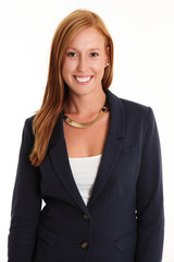Smiling attractive businesswoman in a blue suit with white shirt standing against a white background smiling in red hair.
