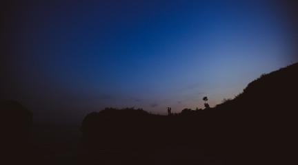 влюблённая пара стоящая в обнимку на фоне  закатного неба в виде силуэтов