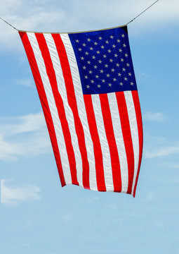 The Amaerican Flag waves in the wind on a blue sky background