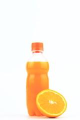 Orange juice in plastic bottle on white background with orange fruit