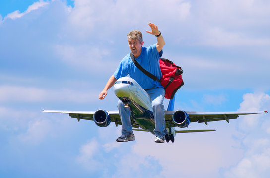 A happy man with a red duffel bag is waving as he flies through the air riding on an airplane like someone would ride a horse - happy frequent flyer flying traveler and travel agency concept.
