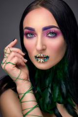 Beautiful girl with evening make-up, green lips in rhinestones and feather neck. beauty face. Photos shot in studio. Close up