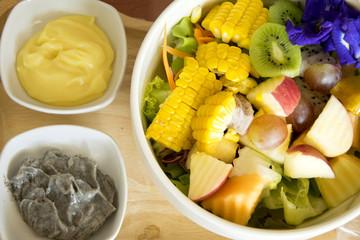 Mix salad fruit and vegetable with black sesame dressing and egg dressing.