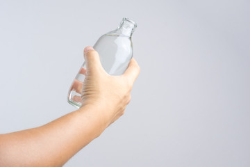 Hand holding glass water bottle