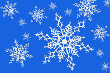 White plastic snowflake ornaments on blue background