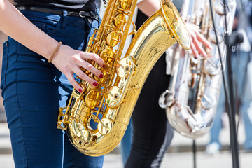 young woman playing saxophone during street fest performance