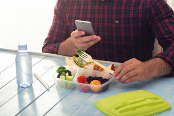 Man photographing lunch box with healthy food sitting at table