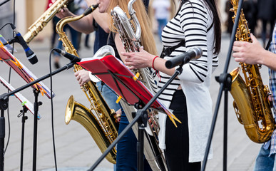 quartet of young musicians playing saxophones during outdoor performance