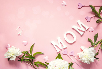 Mothers day background with white peonies and decorative hearts on pink table.