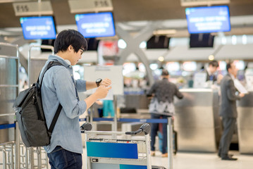young asian man waiting for check in and dropping his luggage at airline check-in counter of international airport terminal