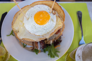 Beer and famous hamburger with fried eggs, beef and bacon at an cafe in Annecy.  France