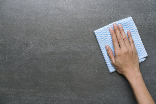 Cleaning black table by woman hand