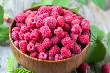 Fresh raspberry with leaves in a wooden bowl