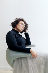 Young plus size female model in tutu skirt sitting in chair stretching her dark curvy hair in bright empty room. Composition with copy space