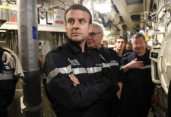 """French President Macron looks on as he stands with crew of the submarine """"Le Terrible"""" and Chief of the Special General Staff Admiral Rogel during a visit to the missile room of the vessel"""
