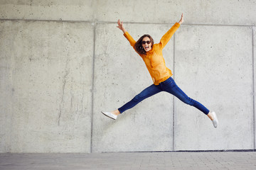 Ecstatic young woman jumping in joy and raising arms in urban outside setting Wall mural