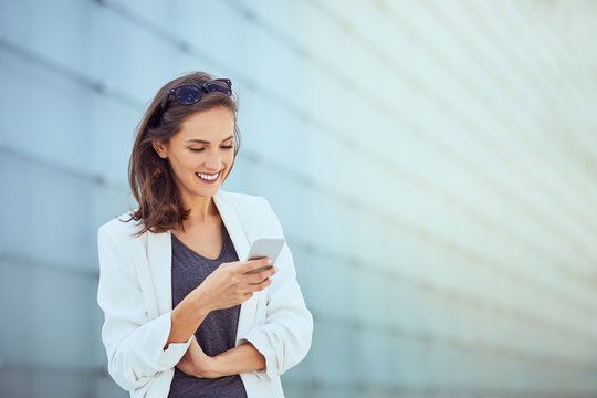 Laughing young businesswoman texting coworker in bright modern outside setting