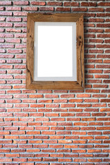 Empty wooden picture frame hanging on a brick wall.