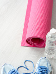 Heart shape Sport shoes, yoga mat, bottle of water on wooden background. Sport equipment. Concept healthy life. Selective focus