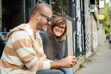 Two young adults using cellphone outdoors.
