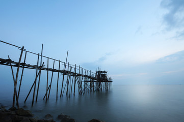 Aluminium Prints Dark grey Old and traditional jetty at a rocky beach in a tropical country during gloomy sunset.