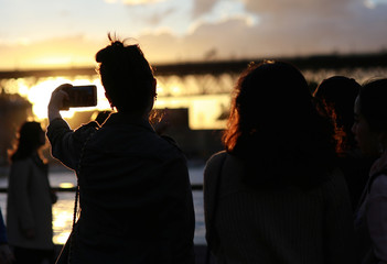 Tourists use their phones to take photographs near the Sydney Opera House at sunset in Australia