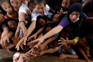 People reach to get ice cream at an evacuation center outside the city as army troops continue their assault against insurgents from the Maute group in Marawi city