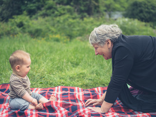 Grandmother and grandchild on picnic blanket