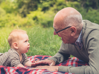 Senior man playing with grandchild on picnic blanket