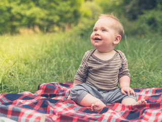 Cute little baby in nature on picnic laughing