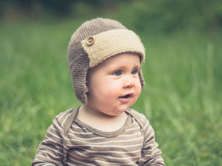 Cute little baby weearing a hat in nature